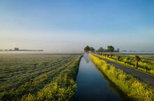 Early Morning View Of Fields And Path Along Drainage Ditch In Coastal Area Of The Netherlands In Spring.