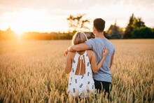 Rear View Of Young Couple Standing In Golden Wheat Field, Hugging.