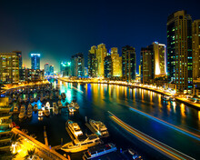Night Scene Of City Skyline And Boats Moored At Harbour, Dubai