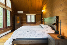 Interior View Of Master Bedroom With King Size Bed Inside A Log Home, Quebec, Canada.