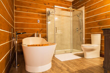Interior View Of Bathroom With Freestanding Tub And Wood Cladding On Walls And Floor In A Log Home