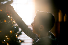 Young Boy Decorating Christmas Tree At Home