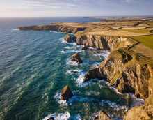 Aerial View Of Bedruthan Steps In Cornwall, Small Secluded Beach With Steep Cliffs And Rock Stacks Offshore. High Tide.