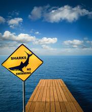 Close Up Of Yellow Shark, No Swim Sign On A Jetty At A Lake, Cagliari, Sardinia, Italy.