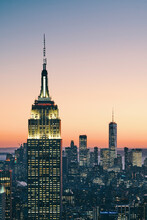 View Of Manhattan Skyline With Illuminated Empire State Building At Sunset, New York City