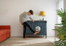 Boy Playing On His Own With A Ball In The Living Room Due To Corona Measures.