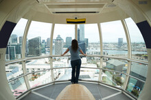 Rear View Of Woman Standing In Melbourne Star Ferris Wheel, Looking At City Skyline, Australia.