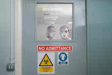 Scientists In Isolation Environment Wearing Masks With Biological Hazard In Research Laboratory.