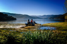 Two People Riding Motorcycles Through Shallows On Gusana Lake, An Artificial Lake In The Territory Of Gavoi, Sardinia, Italy.