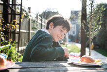 Ssmiling Boy Wearing Green Jumper Sitting At A Table In A Garden With A Snack.