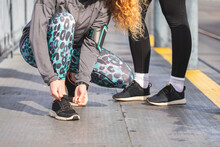 Close Up Of Two Female Joggers, Tying Shoelaces Of Black Trainers.