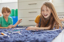 Boy And Girl Lying On Blue Rug, Drawing With Colouring Pencils.