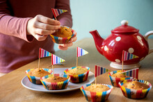 High Angle View Of Red Tea Pot And Decorated Cupcakes On A Kitchen Table.