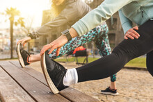Two Young Women In Sportswear Standing In A Park, Stretching After Jogging.