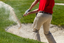Male Golfer Chipping Out Of Sand Trap.