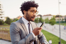 Portrait Of Businessman Wearing Glasses And Grey Suit, Using Mobile Phone.