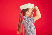 Portrait Of Brunette Girl Wearing Blue Top And Sailor's Hat On Red Background.