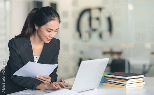 Young smart businesswoman working on laptop and paperwork with happiness while sitting at office desk.
