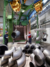 Men Working In A Steel Factory, Lifting U-bend Tubes On Winches.
