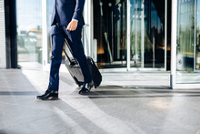 Low Section Of Businessman Walking With Black Trolley Through Revolving Glass Door.
