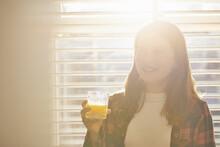 Teenage Girl Standing In Front Of Window, Holding Glass Of Orange Juice.