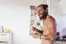 Bearded Tattooed Shirtless Man With Long Brunette Hair Standing In A Kitchen, Laughing.