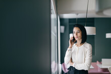 Young Businesswoman In Hotel Making Smartphone Call