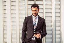 Portrait Of Bearded Businessman Wearing Dark Suit, Checking Mobile Phone.