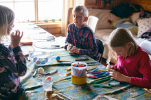 Boy And Two Girls Sitting At A Table In A Log Cabin, Doing Handicrafts, Vasterbottens Lan, Sweden.