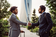 Two Businessmen Wearing Suits Standing Outdoors, Shaking Hands.