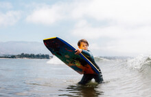 Portrait Of Young Boy Wearing Wet Suit In Ocean, Holding Bodyboard, Waiting For Wave, Santa Barbara, California, USA.