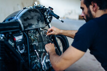 Young Male Motorcyclist Repairing Vintage Motorcycle Outdoors