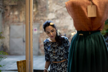 Woman With Long Black Hair Looking At Skirt On Mannequin In Shop Window.
