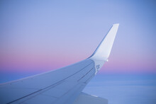 View Along Passenger Plane Wing Flying Above Clouds At Sunset.