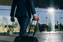 Businessman With Wheeled Luggage Walking Towards Glass Building, Malpensa, Milan