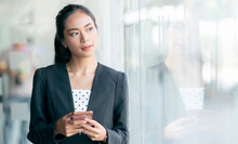 Portrait Of Young Asian Businesswoman Looking Outside And Using Smartphoe While Standing In Office.