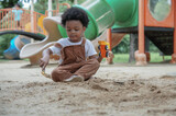 African little boy with afro hair enjoy playing sand on playground outdoors. Adorable kid having fun with sand and toys loader in the park on a sunny day