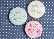 Three Happy Birthday Cookies Arranged On A Polka Dot Table Cloth