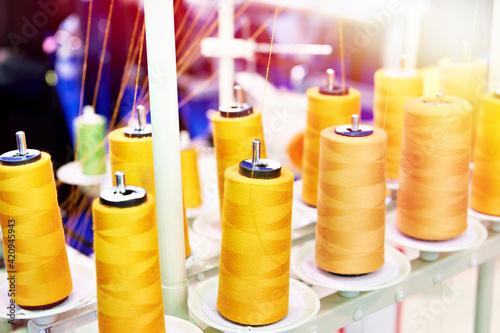 Obraz na plátne Orange spools of thread in sewing workshop