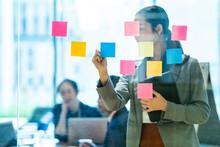付箋にアイディアを出し合いアイディアを検討する社員たち