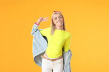 Happy Young Woman Showing Victory Gesture On Color Background