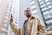 Businessman Holding A Mobile Phone In His Hand Between Buildings