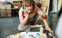 Creative Female Artist Sitting On The Floor In The Art Studio And Painting On Paper With A Paintbrush. A Woman Student Painter In Eyeglasses Painting With Watercolors In Her Workshop.