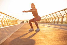 Athletic Red Head Woman Doing Squats With An Expander