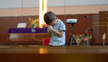Young Christian Asian Boy Standing On Church Chairs Praying To God With Hope And Faith