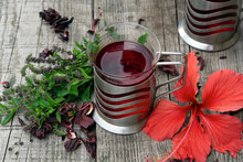 Two Glass Cup Of  Red Herbal Hibiscus Tea With Ingredients  On Wooden Table  Against A Blurred Green