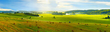 Summer Panoramic Natural Landscape. Wide Panorama Of Countryside With Serpentine Road And Green Meadows And Forests On Hills With Beautiful Lighting. Straw Bales In Foreground.