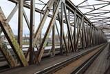 Stalowe zardzewiałe, elementy mostu kolejowego nad rzeką.