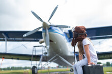 A Little Girl In A Pilot's Costume Sits On A Suitcase Against The Background Of An Airplane With A Propeller. Child Dreams Of Flying In The Sky