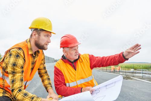 Obraz Bauleiter und Vorarbeiter mit Plan zur Bebauung - fototapety do salonu